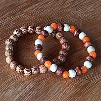 Beaded stretch bracelets, 'Orange Connection' (pair) - Hand Crafted Bead Stretch Bracelets from Bali Artisan (Pair)
