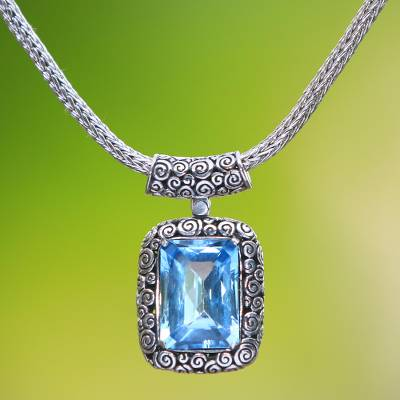 Blue topaz pendant necklace, 'Buddha Curl Memories' - Blue Topaz and Sterling Silver Pendant Necklace from Bali