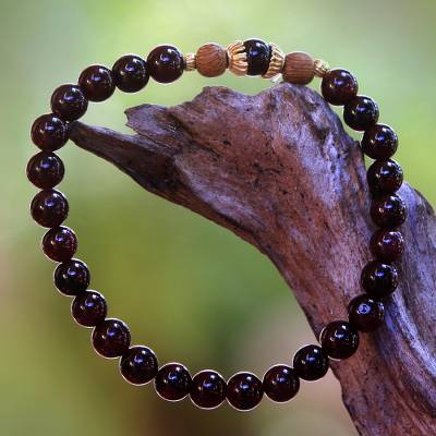 Gold accented garnet beaded stretch bracelet, 'Batuan Tune' - Gold Accented Garnet Beaded Stretch Bracelet from Bali