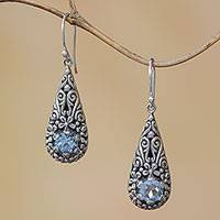 Blue topaz dangle earrings, 'Hopeful Swirls' - Bali Sterling Silver and Blue Topaz Plumeria Dangle Earrings