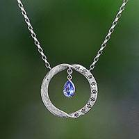 Blue topaz pendant necklace, 'Paw Twist' - Animal-Themed Blue Topaz Circular Pendant Necklace from Bali