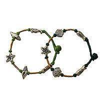 Cord wristband bracelets, 'Green Ocean' (pair) - Handcrafted Gold and Green Charm Wristband Bracelets (Pair)