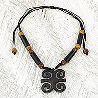 Ebony wood pendant necklace, 'Ram's Horns' - African Ebony and Sese Wood Ram's Horn Adinkra Necklace