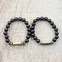 Recycled glass bead stretch bracelets, 'Ebony Duo' (pair) - Black and Gold Recycled Bead Stretch Bracelets (Pair)