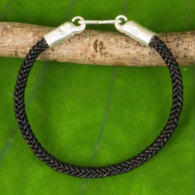 Braided leather bracelet, 'Elephant Promise in Black' - Braided Leather Cord Bracelet with Silver Elephant Clasp