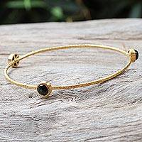 Gold plated onyx bangle bracelet, 'Orbit of Beauty' - Artisan Crafted 18k Gold Plated Bangle with Black Onyx