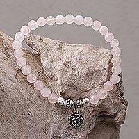 Rose quartz beaded stretch bracelet, 'Still Rose' - Rose Quartz and Flower Charm Beaded Bracelet from Bali