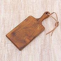 Teakwood cutting board, 'Dinner Party' - Teakwood and Leather Accent Handcrafted Cutting Board