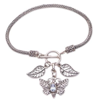 Blue topaz charm bracelet, 'Beaming Butterfly' - Sterling Silver and Blue Topaz Butterfly Charm Bracelet