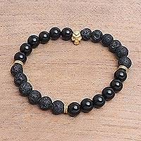 Gold accented onyx beaded stretch bracelet, 'Dark Skull' - Gold Accented Onyx Skull Beaded Stretch Bracelet from Bali