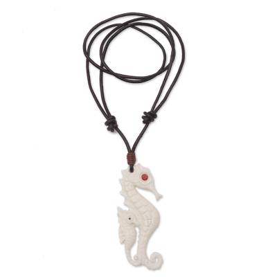 Bone and garnet pendant necklace, 'Caring Seahorse' - Bone and Garnet Seahorse Pendant Necklace from Bali