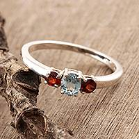 Garnet and blue topaz 3-stone ring, 'Passionate Embrace' - Handcrafted Sterling Silver Gemstone Ring from India