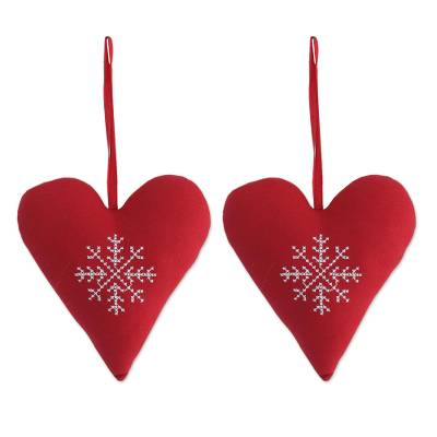 two handmade heart shaped cotton ornaments in red from india
