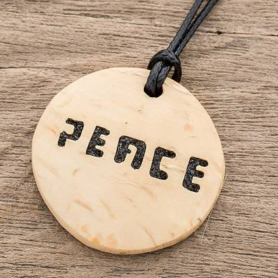 Coconut shell and lava stone pendant necklace, 'Have Peace' - Peace-Themed Coconut Shell and Lava Stone Pendant Necklace