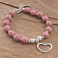 Rhodonite beaded charm bracelet, 'Love Fascination' - Rhodonite Beaded Bracelet with Heart Charm from Peru