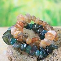Beaded stretch bracelets, 'Green Orange Odo Tintine' (pair) - Beaded stretch bracelets (Pair)
