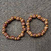 Wood stretch bracelets, 'African Grace' (pair) - 2 Red and Brown Floral Beaded Wood Stretch Bracelets