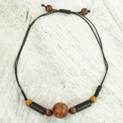 Wood pendant necklace, 'Round Might' - Sese Wood and Bamboo Cord Pendant Necklace from Ghana