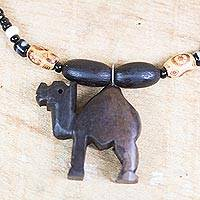 Ebony wood and recycled glass beaded pendant necklace, 'Gazing Camel' - Ebony Wood and Recycled Glass Camel Necklace from Ghana