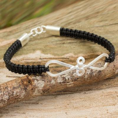 Leather and sterling silver braided bracelet, 'Black Infinity Swirl' - Thai Black Leather Braided Bracelet with Sterling Silver